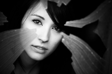 Woman looking through dirty broken glass photo