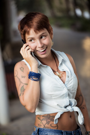 Young beautiful woman cheerfully speaking on phone on the street. photo