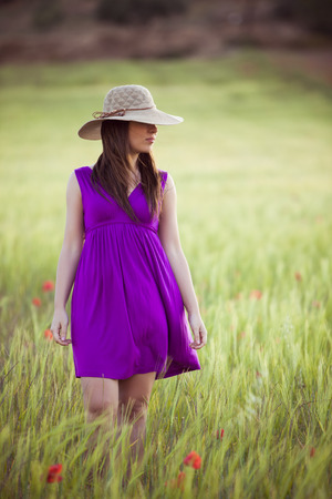 Young girl on field hiding her eyes below her hat. photo