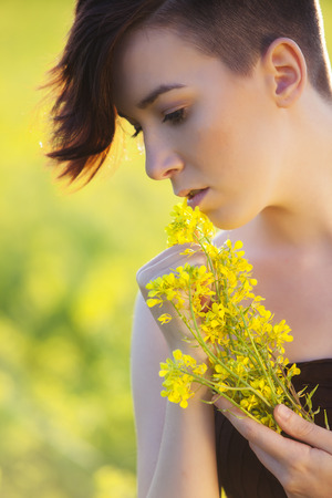Young girl portrait holding yellow flowers