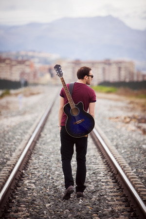 vagabond: Young male musician walking with his acustic guitar.