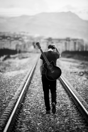 railway points: Young male musician walking with his acustic guitar.