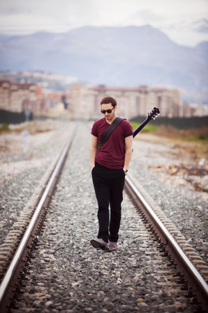 Young male musician walking with his acustic guitar. photo