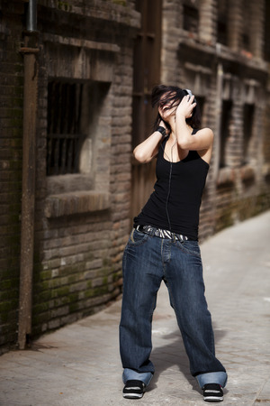 Young beautiful girl listening to music on urban background