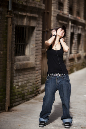 Young beautiful girl listening to music on urban background Stock Photo - 27084203