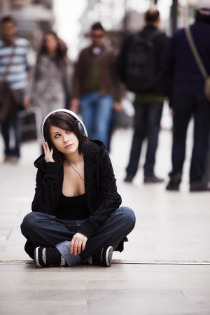 Young girl with headphones sitting on sidewalk photo