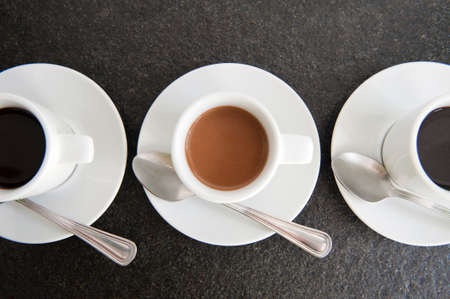 clave: Three white coffe cups, only one have coffe with milk. Its your choice with or without milk.