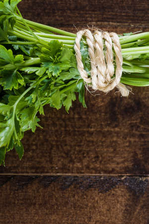 clave: bunch of parsley over dark wood table