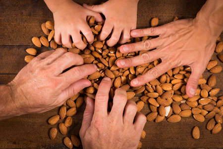 clave: Some hands taking almonds from over the table