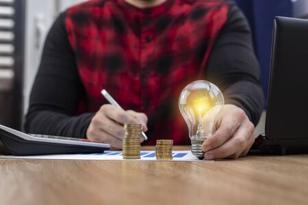 lit bulb with money and a calculator representing business ideas Banque d'images