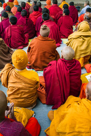 Small group of buddhist praying monks seen from behind in Lumbini, Nepal. Wear colorful thick robes and beanies in winter time for keeping warm Editorial