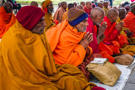 Lumbini, Nepal - December 21st 2012. Austere experienced old nepali buddhist monk prays sits in a row amongst others. wear thick robes and beanie hat in winter