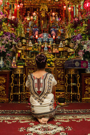 A lady worships her gods before an over-saturated altar full of religious items, Hanoi, Vietnam Éditoriale