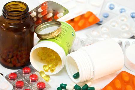 Particolare delle bottiglie della medicina con le pillole rovesciate.