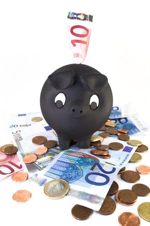Piggy bank looking at euro bills and coins. photo