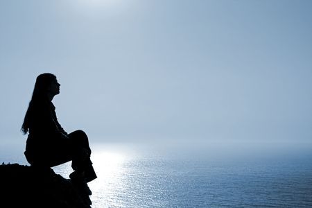Meditating woman silhouette against seascape.