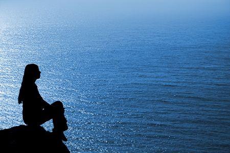 introspective: Meditating woman silhouette against seascape.