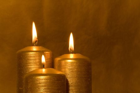 introspective: Three golden candles burning in the grunge background