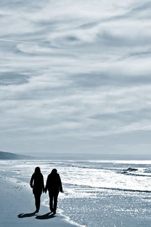 union beach: two women walking at the beach in the winter