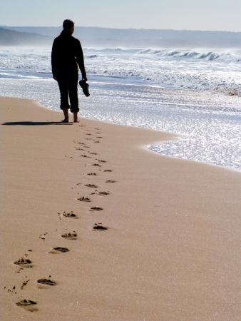 foot path: Woman walking alone at the beach