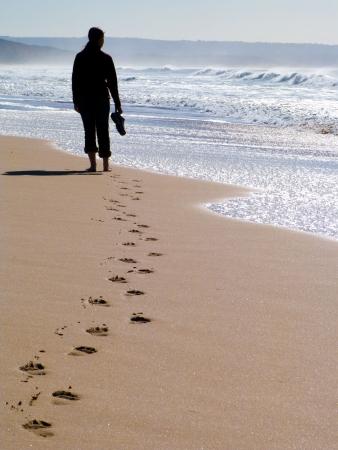walking path: Woman walking alone at the beach