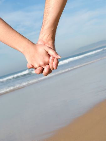 Lovers couple holding hands on beach at winter