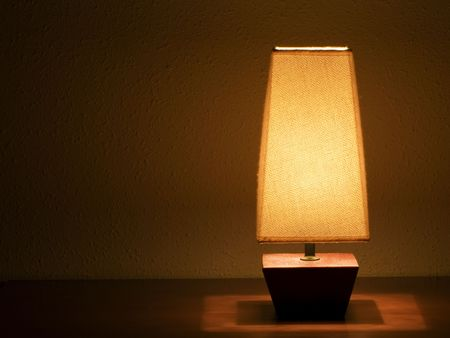 bedside: Lit bedside lamp over nightstand   Stock Photo
