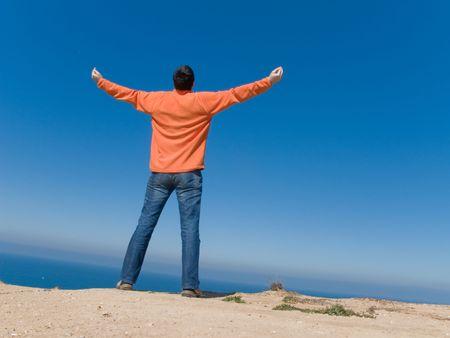manos levantadas al cielo: hombre joven con los brazos abiertos