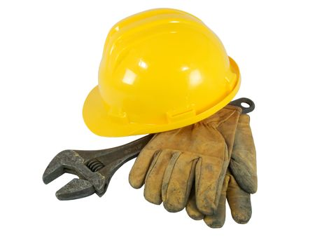 Yellow hardhat, old leather gloves and wrench isolated on white background   photo