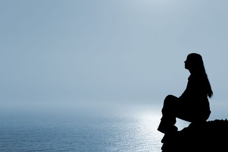 blue sky thinking: Meditating woman silhouette against seascape.
