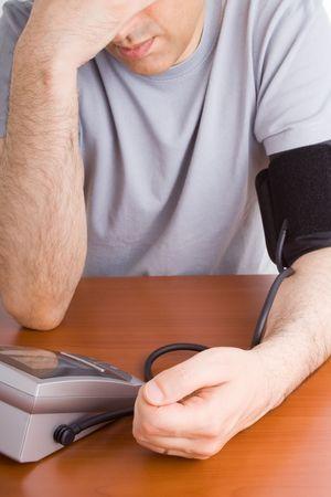 Man feeling sick checking his blood pressure photo