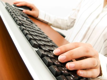 Businesswoman typing in the computer keyboard and using a mouse Stock Photo - 3184980