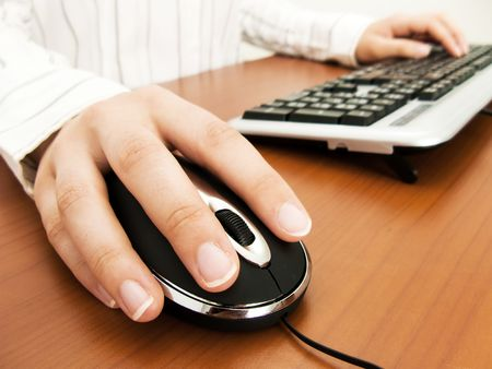 Businesswoman typing in the computer keyboard and using a mouse Stock Photo - 3185008
