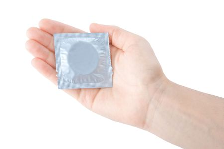 birth prevention: Hand holding a condom isolated on white background