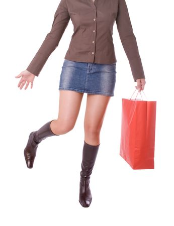 Young attractive woman running and carrying a shopping bag