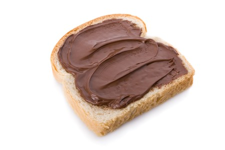Hazelnut and chocolate spread over a slice of bread