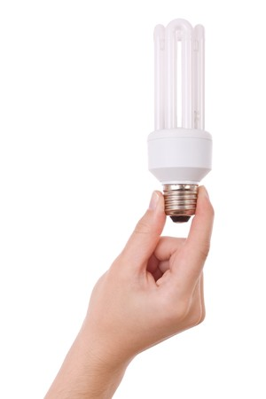 Hand holding compact fluorescent light bulb isolated on white photo