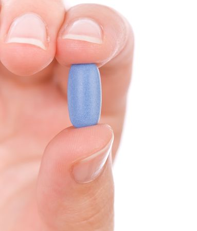 inhibition: Hand holding a blue pill close up