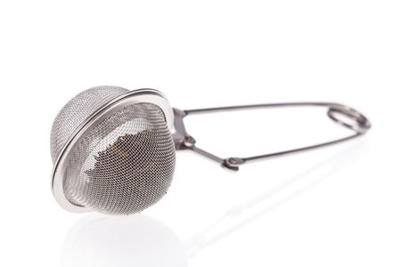 tea filter: Tea infuser with Green Tea leaves isolated on a white background