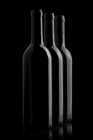 Three elegant wine bottles in a black background Stock Photo