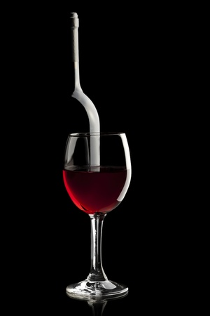 glass of red wine: Elegant red wine glass and a wine bottle in black background