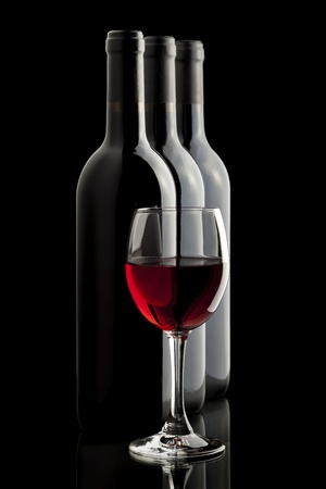 three objects: Elegant red wine glass and a wine bottles in black background