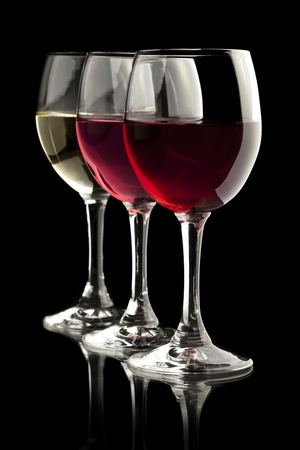 Elegant red, rose and white wine glasses in a black background