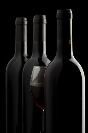 Elegante calice di vino rosso e un bottiglie di vino a sfondo nero Archivio Fotografico - 9296746