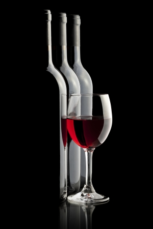 Elegante bicchiere di vino rosso e un bottiglie di vino a sfondo nero Archivio Fotografico - 15707376