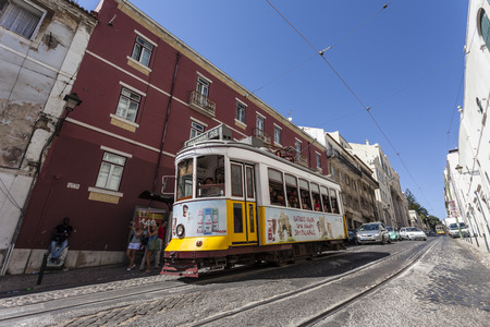 electrico: Lisbon, Portugal - September 15, 2013  The iconic number 28 Tram line with an old Lisbon Tram crossing the medieval, Alfama District