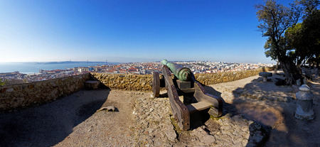 castle district: Sao Jorge  St  George  Castle in Lisbon, Portugal  Old Bronze cannon and a view of Lisbon's Baixa  downtown  District and river