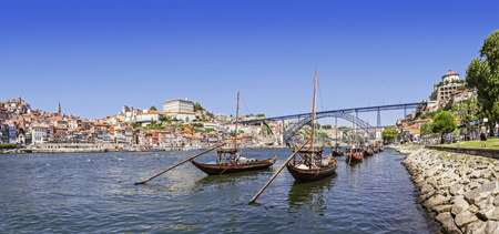 The iconic Rabelo Boats, the traditional Port Wine transports, with the Ribeira District and the Dom Luis I Bridge over the Douro River  Porto, Portugal  Unesco World Heritage
