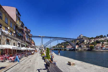 Porto, Portugal - July 27, 2013  Tourists and locals enjoy the Ribeira District scenery and summer sun in the Douro River bank near the Dom Luis I Bridge in Porto, Portugal  Unesco World Heritage  Editorial