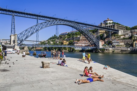 Porto, Portugal - July 27, 2013  The typical local children of the Ribeira District sunbathing after a swim in the Douro river near the Dom Luis I Bridge in Porto, Portugal  Unesco World Heritage